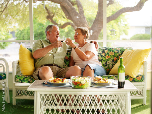 elderly couple drinking wine with their dinner