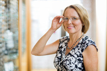 Happy Woman Trying On Eyeglasses In Store