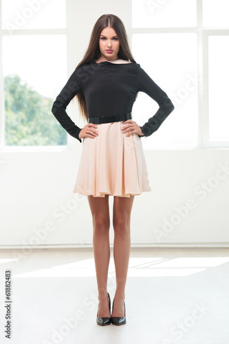 young fashion woman holds hands on hips