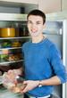 guy  near opened refrigerator in kitchen