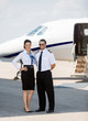 Stewardess And Pilot Standing Against Private Jet