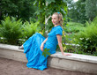 young beautiful woman in a blue dress in the arbor twined