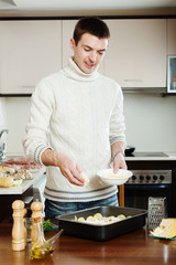 Handsome man adding grated cheese in roasting pan