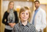 Confident Boy With Optometrist And Mother At Store