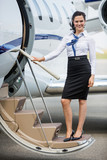 Stewardess Standing On Ladder Of Private Jet