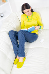 A young woman lying on the sofa reading book