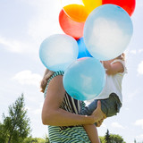 Mother And Daughter With Balloons In Park