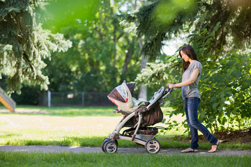 Mother Pushing Stroller In The Park