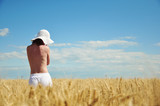 Naked woman with white hat in wheat field