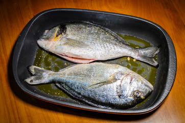 A pair of sea bream ready to be cooked in the oven