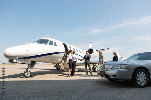 Leinwanddruck Bild Corporate People Greeting Airhostess And Pilot At Terminal