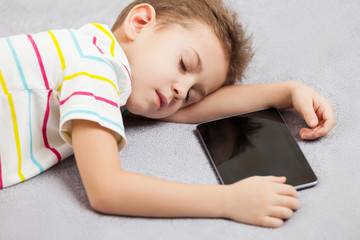 Tired sleeping child boy holding tablet computer