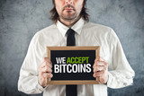 Businessman holding board with title WE ACCEPT BITCOINS