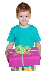 Red-haired young boy holds a gift box
