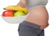 Pregnant woman showing fruit bowl to camera