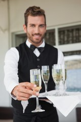 Handsome waiter offering flute of champagne