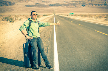 Young handsome man hitch-hiking in the Death Valley - California