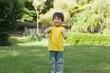 Young boy gesturing thumbs up in park