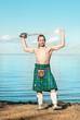 Scottish man with sword near the sea