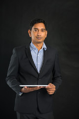 indian business man with tablet on dark background