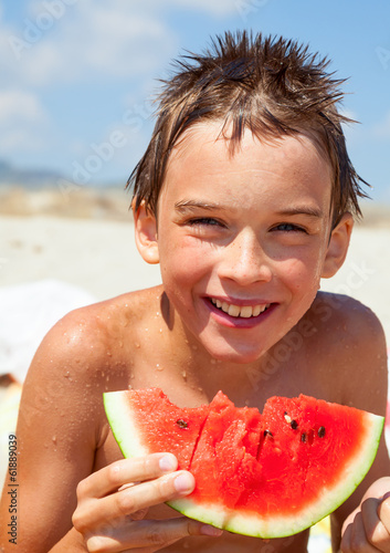 Boy eating melon on a beach