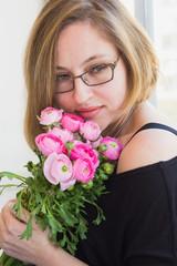 Closeup portrait of elegant middle aged woman holding flowers.