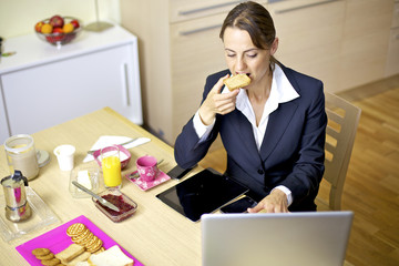 Beautiful woman working at home with computer during breakfast
