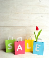 Pastel colors shopping bags with red tulip