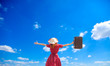 Young girl with suitcase on blue sky background