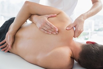 Physiotherapist massaging man