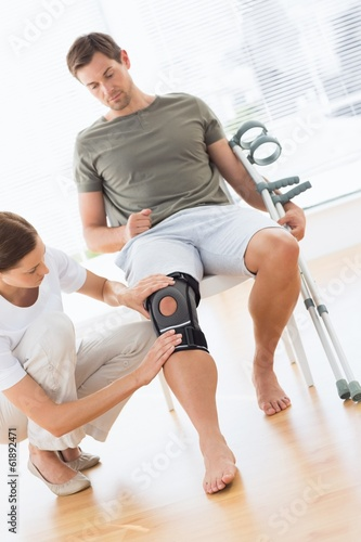 Physiotherapist checking man with crutches