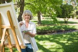 Smiling mature woman painting in park