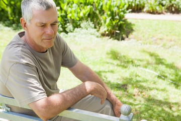 Thoughtful mature man sitting on park bench