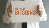 Businessman holding paper board with title WE ACCEPT BITCOINS.