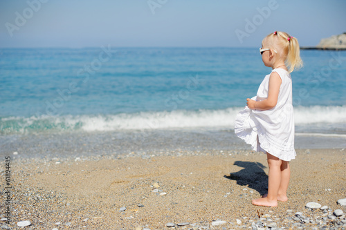 Little girl standing at the sea...