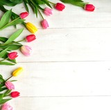 Colorful tulips on white wooden background