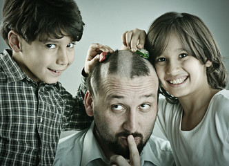 Kids playing with cars on father's head as a road