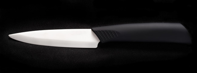 White ceramic knife on a black background.