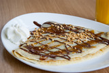 Delicious  nugat, caramel and peanuts pancake decorated with whi