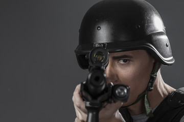 Assault, paintball sport player wearing protective helmet aiming