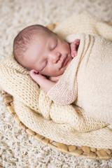 Newborn Baby eingewickelt liegend