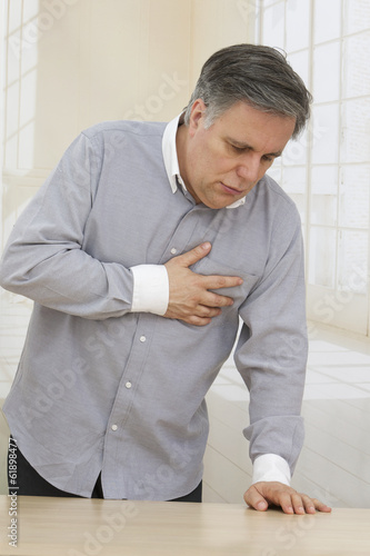 A mature man having a heart pain in his living room