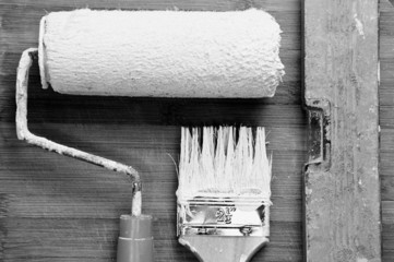 Painting tools stained in white paint on the background of woode