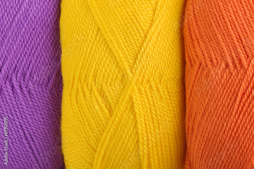 background of yarn skeins in yellow, orange and purple colors