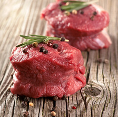 raw steak with pepper on wood