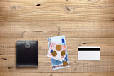Wallet, money and plastic card on wooden background