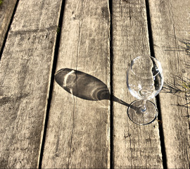 glass goblet lies on the old boards