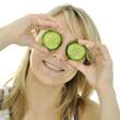 Frau hält Gurken-Scheiben vor Augen