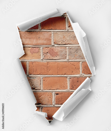 Hole ripped paper and brick wall