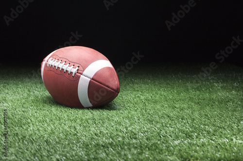Football on grass against dark background
